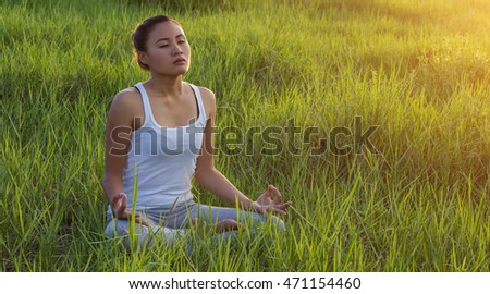 Yoga in the city: beautiful young fit woman wearing sportswear meditating, breathing, sitting with crossed legs in Half Lotus Posture on the street on summer day, Ardha Padmasana, copy space