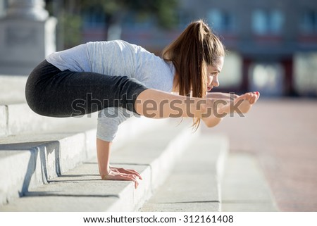 Yoga in the city: beautiful young fit woman wearing sportswear working out on the street on summer day, doing handstand, variation of Firefly posture, Tittibhasana, full length, profile view - stock photo
