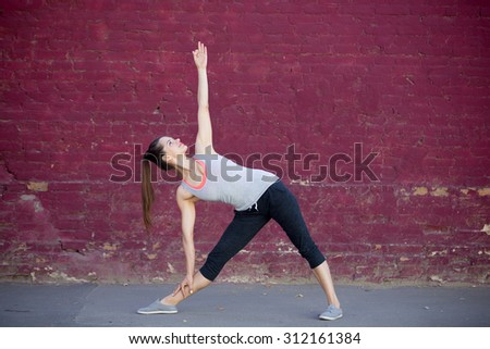Yoga in the city: smiling beautiful sporty young woman working out on summer day on the street in front of old red brick wall, doing Utthita Trikonasana, Extended Triangle posture - stock photo