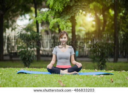 Yoga in the park, outdoor with effect light, healthy woman.  Concept of healthy lifestyle and relaxation.
