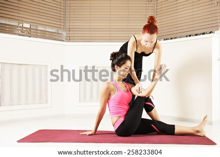 Yoga instructor corrects student's pose moving her hand - stock photo
