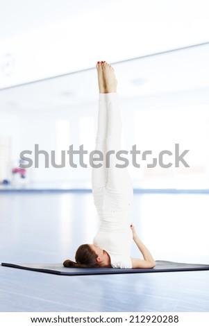 Yoga instructor doing exercise on yoga mat in studio. - stock photo