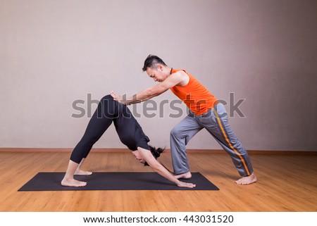 Yoga instructor guiding student perform downward facing dog pose or Adho Mukha Svanasana - stock photo