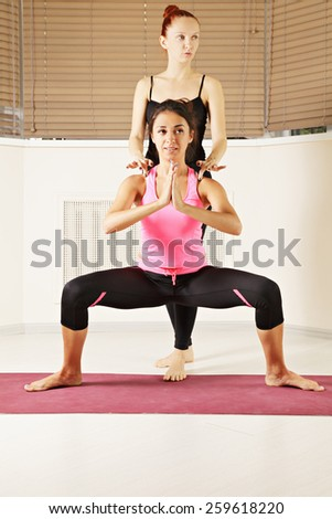 Yoga instructor helping brunette in standing pose - stock photo
