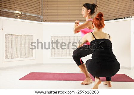 Yoga instructor helping brunette take standing pose - stock photo