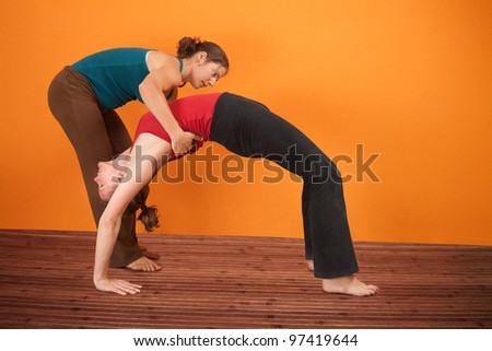 Yoga instructor helps student perfrom Urdhva Dhanurasana over orange background - stock photo