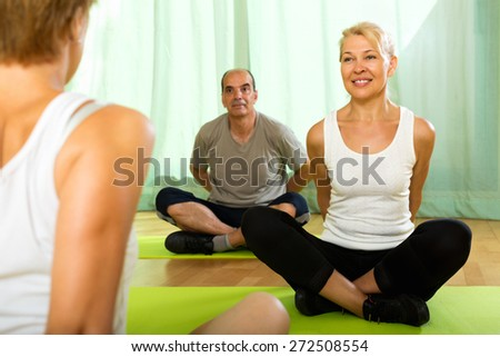 Yoga instructor showing asana to active  senior attenders - stock photo