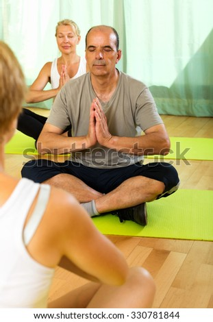 Yoga instructor showing asana to positive senior attenders - stock photo
