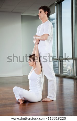 Yoga instructor teaching yoga positions to young woman at gym - stock photo