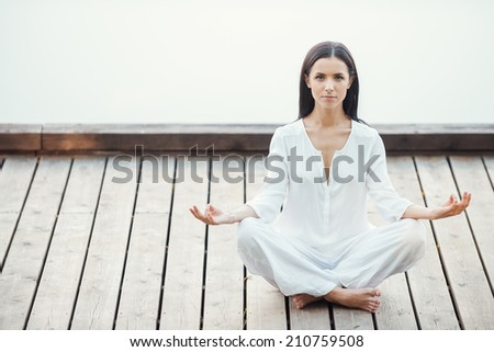 Yoga is my life. Beautiful young woman in white clothing meditating on seaside  - stock photo