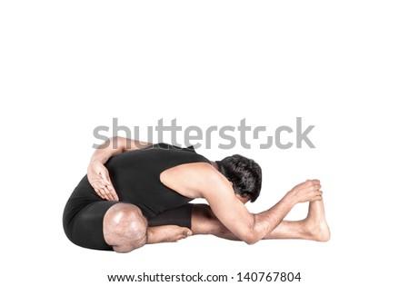 Yoga Janu Sirsasana forward bending pose by Indian man in black costume isolated at white background - stock photo