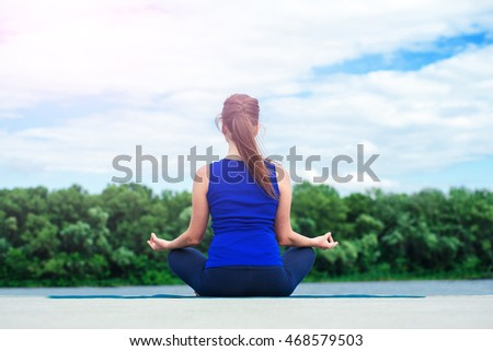 Yoga lotus. Young woman doing yoga by the lake, sitting turned her back. located on the docks.  Concept healthy lifestyle. Lots of copy space. Selective focus
