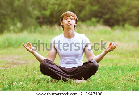 Yoga man relaxation outdoors on the grass  - stock photo