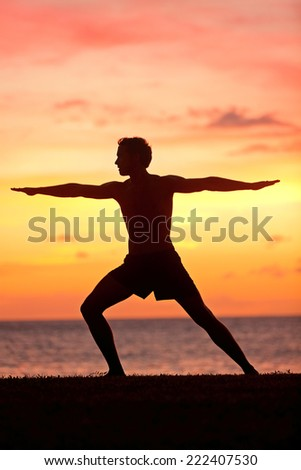 Yoga man training and meditating in warrior pose outside by beach at sunrise or sunset. Male yoga instructor working out training in serene ocean landscape. Silhouette of man model against sun.