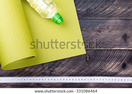 Yoga mat, water bottle and measuring tape on a wooden background. Equipment for yoga. Concept  healthy lifestyle. Selective focus - stock photo