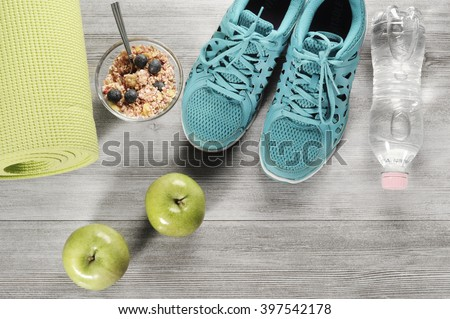 yoga mat with sport shoes and healthy food on a wooden background - stock photo