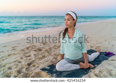 Yoga mat woman stretching hip, hamstring muscles and groin area, leg muscles with pigeon pose stretch. Fit Asian fitness athlete girl exercising sports stretches in activewear on beach at sunset. - stock photo