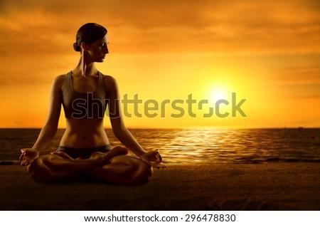 Yoga Meditating Lotus Position, Exercising Woman Meditation in Asana Pose, Female on Sunrise Beach - stock photo