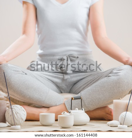Yoga meditation at home. Relaxation concept with unrecognizable spiritual young woman sitting in front of candles, tea and aromatic sticks - stock photo