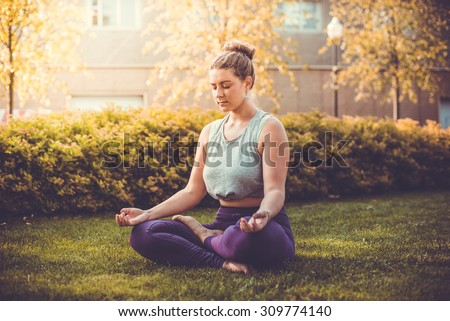 Yoga meditation in lotus pose in park.  Young woman in peace, soul and mind zen balance concept. Toned picture - stock photo