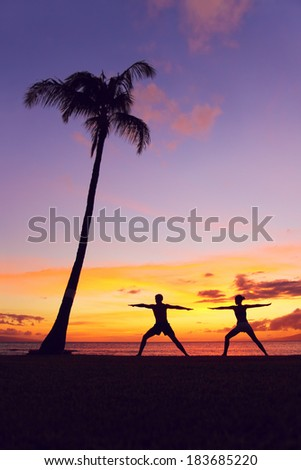 Yoga meditation people meditating training warrior pose outside by beach at sunrise or sunset. Woman and man yoga exercising training in serene ocean landscape. Silhouette of couple against sunset - stock photo
