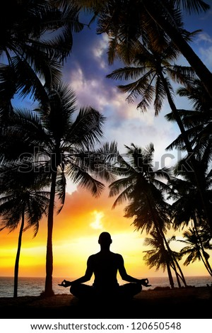 Yoga meditation silhouette by man at palms, ocean and sunset sky background in India - stock photo