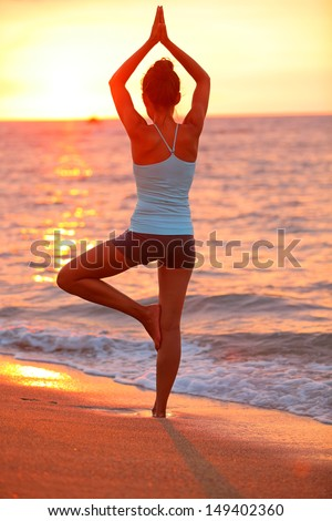 Yoga meditation woman meditating at beach sunset relaxing in yoga posture, tree pose, vrksasana. Relaxed serene Asian woman enjoying evening sun light and sunshine. From Big Island, Hawaii, USA. - stock photo