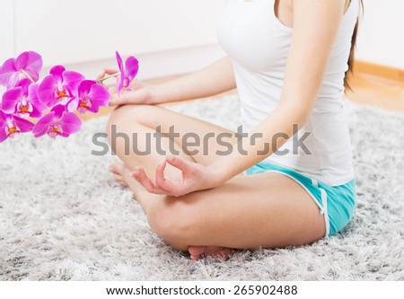 Yoga Meditation Woman Relaxing at home.Healthy Lifestyle in Lotus Posture .Unrecognizable caucasian female meditate  on the floor. - stock photo