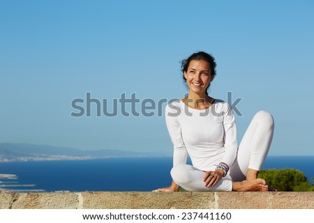 Yoga on high altitude with big city on background, smiling woman seated in yoga pose on amazing city background, woman meditating yoga and enjoying sunny evening, woman makes yoga on mountain hill - stock photo