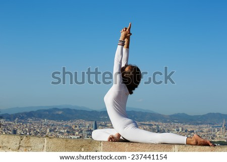 Yoga on high altitude with big city on background, woman stretching seated in yoga pose on amazing city background, woman meditating yoga and enjoying sunny evening, woman makes yoga on mountain hill - stock photo