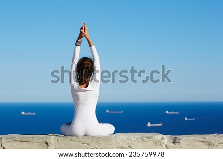 Yoga on high altitude with sea with ships on background, woman seated in yoga pose on amazing sea background, woman meditating yoga enjoying sunny evening, woman makes yoga meditation on mountain hill - stock photo