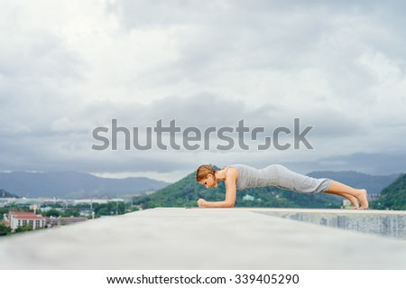 Yoga on rooftop. Happy young woman stretching on roof with city and mountains view. - stock photo