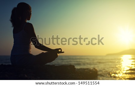 yoga outdoors. silhouette of a woman sitting in a lotus position on the beach at sunset - stock photo