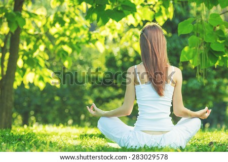 Yoga outdoors. Woman sits in lotus position zen gesturing. Concept of healthy lifestyle and relaxation - stock photo