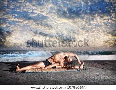 Yoga parivrtta janu sirsasana pose by fit man with dreadlocks on the beach near the ocean at sunset background - stock photo
