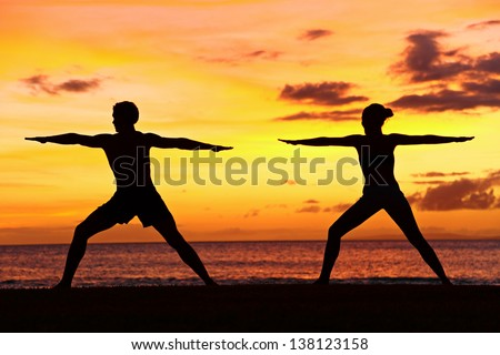 Yoga people training and meditating in warrior pose outside by beach at sunrise or sunset. Woman and man yoga exercising training in serene ocean landscape. Silhouette of couple against sun. - stock photo