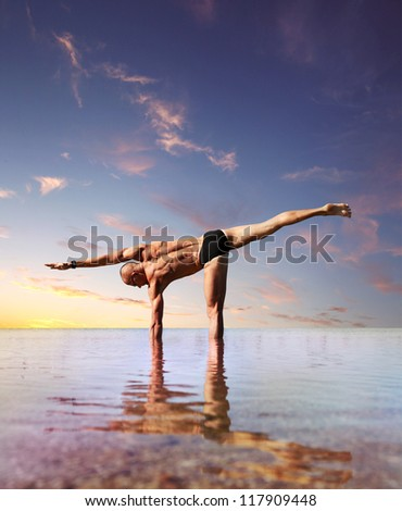 Yoga practice. Man doing lateral stretching yoga exercise standing into the water - stock photo