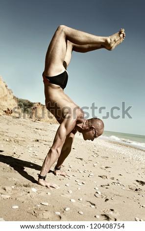 Yoga practice.  Man in scorpion yoga pose on the beach - stock photo
