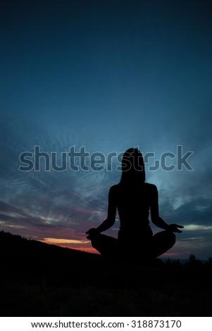 Yoga practicioner during the sunset meditation - stock photo