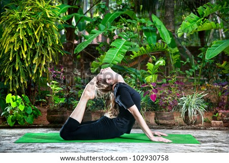 Yoga Raja Kapotasana backward bending pose by woman in black cloth in the garden with palms, banana trees and plants in the pots - stock photo
