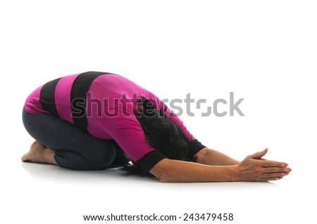 Yoga seria: Mature woman in Balasana yoga pose isolated on white background. Balasana, Child's Pose or Child's Resting Pose is an asana. - stock photo