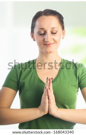 Yoga seria: Woman with closed eyes making Namaste mudra hands gesture - stock photo