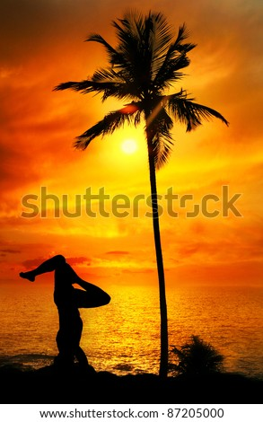 Yoga shirshasana head standing pose by Man in silhouette with palm tree nearby outdoors at ocean and sunset background. Vagator beach, Goa, India - stock photo