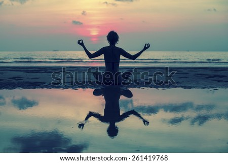 Yoga silhouette. Girl doing meditation in the ocean beach. With reflection in water. - stock photo