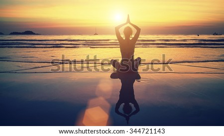 Yoga silhouette. Meditation girl on the background of the stunning sea and sunset. Woman doing meditation near the ocean.
