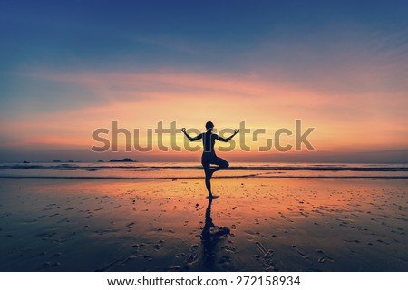 Yoga silhouette. Woman doing meditation near the ocean.  - stock photo