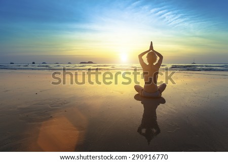 Yoga silhouette. Yoga woman sitting in lotus pose on the beach with reflection during sunset.