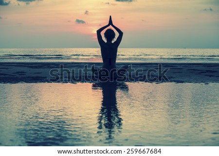 Yoga, silhouette young woman on the beach at sunset, harmony of health. - stock photo
