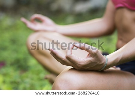 Yoga teacher practicing meditation outdoors - stock photo