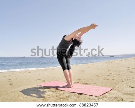 Yoga teacher practising at the beach pose arda chandrasana - stock photo